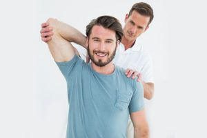 Physiotherapist holding patient's elbow from behind
