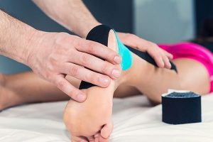 Physiotherapist applying k-tape in patient's ankle